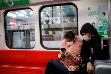 People wearing masks travel in the subway in Beijing on Tuesday, as the country is hit by an outbreak of the new coronavirus. (Reuters photo)