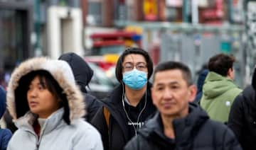 A man wearing a mask walks in the Chinatown district of downtown Toronto.