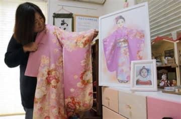 亡くなった松崎胡桃さんのために仕立てた振り袖を持つ母の久美子さん。傍らでは、晴れ着姿の胡桃さんのイラストがほほ笑みかける=熊本市東区