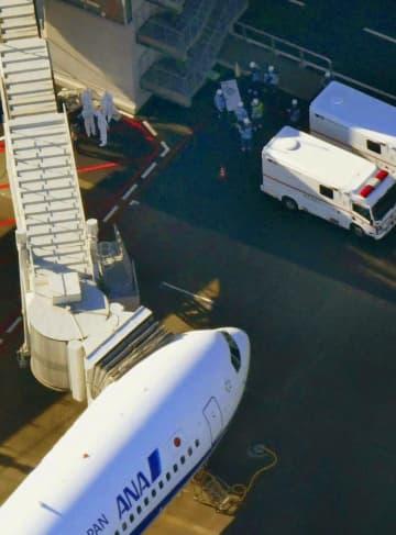中国・武漢から邦人を乗せ羽田空港に到着した日本政府の全日空チャーター機と近くで待機する関係者=29日午前9時27分(共同通信社ヘリから)