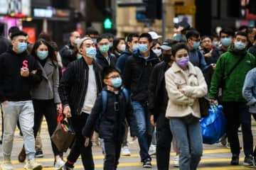 Pedestrians wearing face masks cross a road during the Lunar New Year of the Rat public holiday in Hong Kong on Jan 27 as a preventative measure following the coronavirus outbreak which began in the Chinese city of Wuhan.
