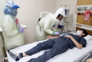 重症患者役の男性の採血をする医師=長崎市、長崎大学病院