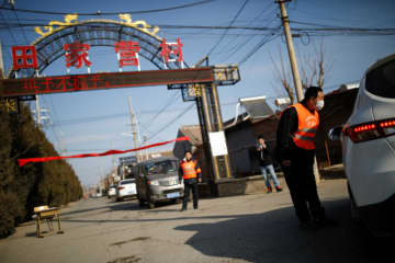 A village committee member speaks to a driver as he guards the entrance of a community in Tianjiaying village, on the outskirts of Beijing, on Wednesday to prevent outsiders from entering, as the country is hit by the new coronavirus. (Reuters photo)