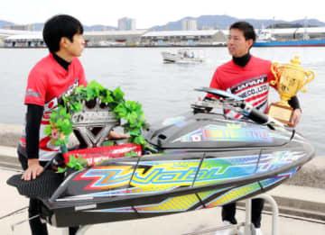 大会で乗った水上バイクの前で、優勝トロフィーを手に渡部監督(左)と大会を振り返る山本さん