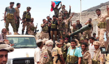 Southern supporters of the Yemeni government flash the victory sign in Khor Maksar, in Aden, as army traded mortar fire with the Houthis militias.
