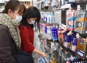 マスクを品定めする女性=29日午後、千葉市中央区のくすりの福太郎千葉中央店