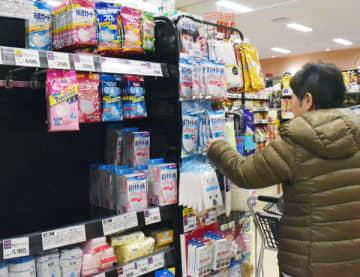 品薄状態の陳列棚でマスクを選ぶ客=29日、さいたま市浦和区のヤオコー浦和上木崎店