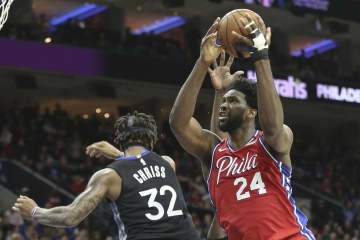 The Philadelphia 76ers' Joel Embiid (24) shoots over the Golden State Warriors' Marquese Chriss (32) on January 28, 2020, at Wells Fargo Center in Philadelphia. - STEVEN M. FALK/The Philadelphia Inquirer/TNS