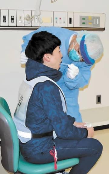 防護服を着て患者役の男性(左)から検体を取る医師