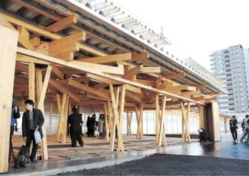 福島県など東北のスギやヒノキが使われたメイン出入り口。右奥は選手村の居住ゾーン=29日、東京・晴海