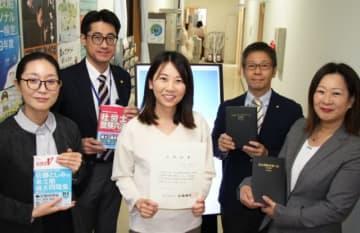 現役生徒で初めて社会保険労務士に合格した麻生恵理子さん(中央)と講師ら=大分市東鶴崎