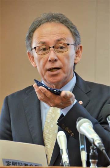 ハンカチを使い、新型コロナウイルスに感染しないための予防法を実演する沖縄県の玉城デニー知事=31日、沖縄県庁