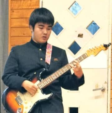 生徒会主催のイベントでエレキギターを弾く與儀浩志さん。「楽しんで弾けて良かった」=22日、那覇市・寄宮中学校体育館