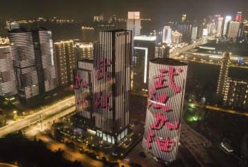 「武漢加油(武漢がんばれ)」の文字が点灯する中国・武漢市内の高層ビル=1月31日(新華社=共同)