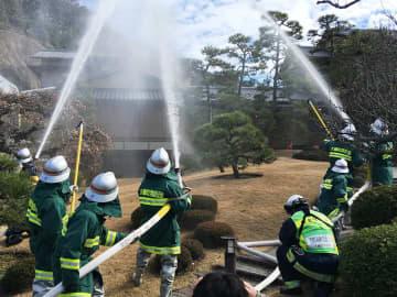 旧吉田茂邸に向けて一斉放水する消防団員ら=県立大磯城山公園