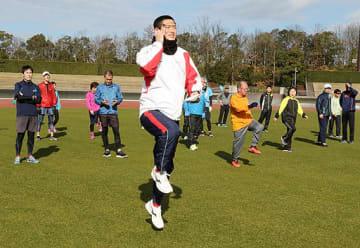 竹田さん(中央)から体の軸を意識したランニングフォームを学ぶ参加者ら=1日、鳥取市のコカ・コーラ陸上競技場