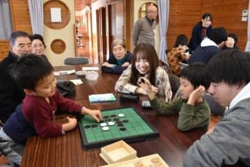 地域食堂「おひさまきっちん」で、ゲームなどをして交流する参加者と学生