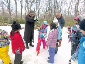 凍った池に穴を開ける子どもたち(提供写真)