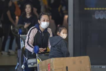 Travellers arrive to LAX Tom Bradley International Terminal wearing medical masks for protection against the coronavirus outbreak on on Sunday in Los Angeles. (AFP photo)
