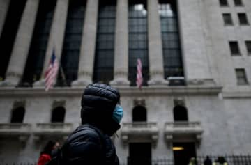 A woman with a facial mask passes the New York Stock Exchange Monday at Wall Street in New York City amid the fear of coronavirus.(JOHANNES EISELE/AFP/)