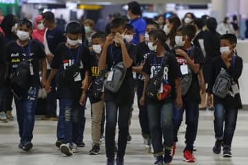 Children wear face masks at Don Mueang airport to protect themselves from the coronavirus outbreak.(Photo by Varuth Hirunyatheb)