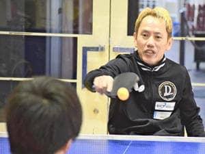 参加者に車いす卓球の楽しさを教える吉田さん(右)