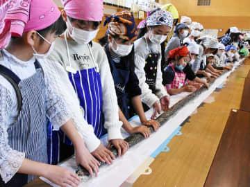 長い恵方巻きを作る児童たち=高山市江名子町、江名子小学校