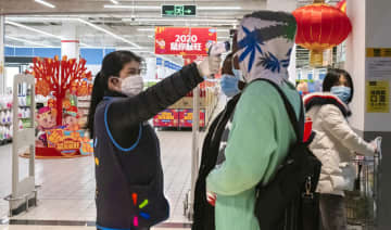 A worker takes the temperature of a customer at the entrance of a Walmart store in Wuhan in central China's Hubei Province.