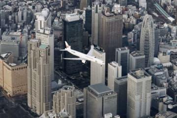 羽田新ルートの飛行確認のため、東京・新宿上空を飛行する航空機=2日