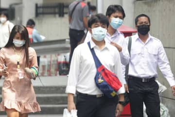 People wear face masks in Bangkok on Monday. PM 2.5 levels again exceeded safety levels in 27 districts on Tuesday. (File photo)
