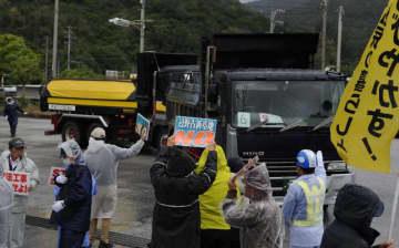 トラックによる土砂搬入に抗議する市民たち=5日午前10時ごろ、名護市安和・琉球セメント桟橋出入り口前