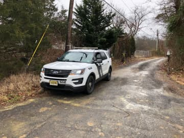 A police vehicle sits at the entrance to a driveway in Deptford Township where police are investigating a missing persons case. (Matt Gray/)