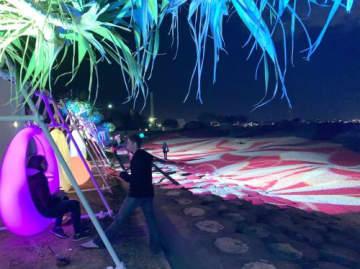 JTB沖縄などの企画「沖縄ナイトビーチin北谷」でライトアップされた夜のサンセットビーチを楽しむ来場者ら=1日、北谷町