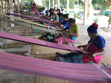 The villagers of Ban Phra Bat Huai Tom in Lamphun province weave cloth in their free time for the village's Otop shop. Karnjana Karnjanatawe