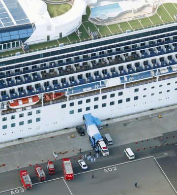 横浜・大黒ふ頭に着岸したクルーズ船「ダイヤモンド・プリンセス」に横付けされた救急車=6日午前11時2分(共同通信社ヘリから)