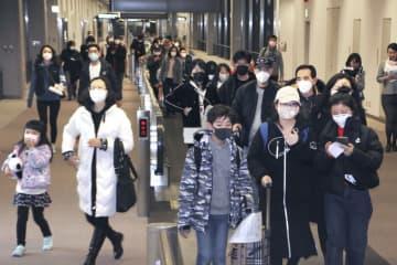 成田空港に到着したマスク姿の乗客ら=1月25日