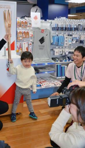 大人に支えられて東京五輪聖火リレーのトーチを手にポーズをとる子どもら=鹿児島市呉服町