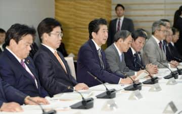 新型コロナウイルス感染症対策本部の会合で発言する安倍首相(左から3人目)=6日午後、首相官邸