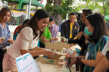 Government spokeswoman Narumon Pinyosinwat (left) sells a bottle of hand wash gel to a customer on Friday morning. (Photo supplied by Wassana Nanuam)