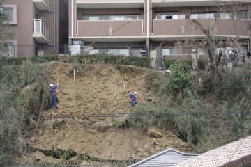 道路脇の斜面が崩落した事故現場を調査する国交省の専門家ら=7日午後、神奈川県逗子市