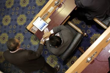 An MP is seen inserting a bunch of voting cards into a device during the vote on the 20202 budget bill in this screenshot captured from a video clip.