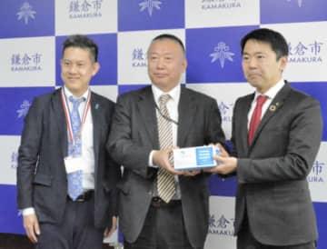 アイネットの社員からマスクの提供を受けた鎌倉市の松尾崇市長(右)=市役所
