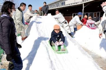 南会津町から届いた雪で造った滑り台を楽しむ園児たち=伊奈町立北保育所