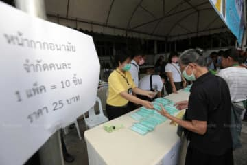 Staff sell face masks at 25 baht for 10 pieces to members of the public near Government House on Friday, the first day masks and bottles of hand sanitiser were offered for sale. (Photo by Chanat Katanyu)