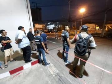 8日、タイ東北部ナコンラチャシマ県の乱射現場付近に立つ警察や市民(AP=共同)