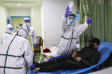 Medical workers move a man into the isolation ward for 2019-nCoV patients at a hospital in Wuhan in central China's Hubei province. (Chinatopix via AP)