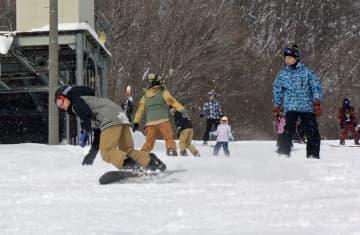 ゲレンデを軽快に滑り降りるスノーボーダーたち