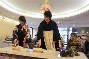 針供養祭で、使われなくなった針を豆腐に刺して労をねぎらう女性=熊本市