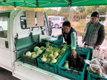 軽トラックに野菜を積んで販売する「軽トラマルシェ」を企画する山崎さん(左)。対面で販売し、旬の野菜のおいしい食べ方も提案する=宇治市広野町・市植物公園