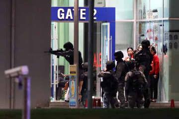 9日、タイ東北部ナコンラチャシマ県で、兵士が立てこもった商業施設に突入する治安部隊員ら(ロイター=共同)